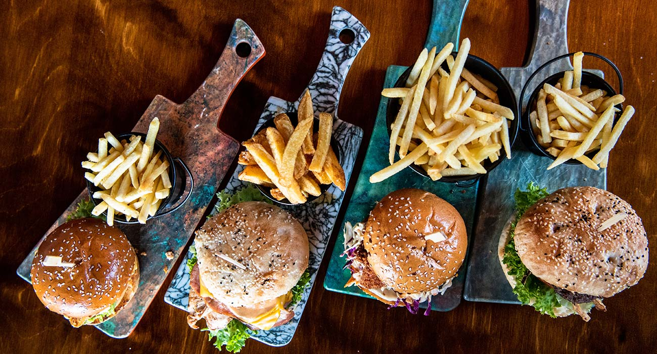 4 sets of burgers and fries placed on a wooden tray as one of the wholesale bakery Perth products.